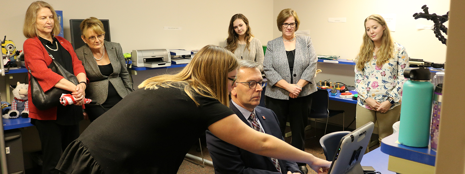 Chancellor Ronnie Green receives instructions from Abby Crimmins, a speech-language pathology graduate student, on how to use the eye gaze system in the AAC Lab as several people look on.
