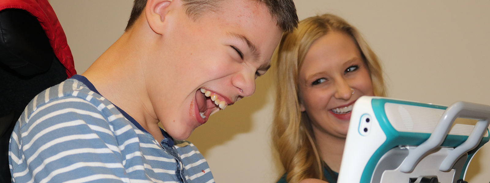 Kaden Bowen and speech-language pathology graduate student Audrey Hartwell share a laugh during Kaden's session at the Barkley Speech Language and Hearing Clinic.