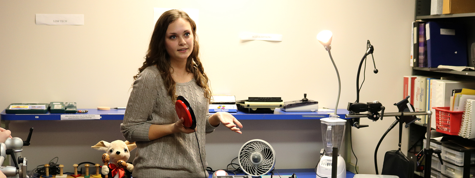Madison Routier, a speech-language pathology graduate student explains various AAC methods and devices in the AAC Lab.