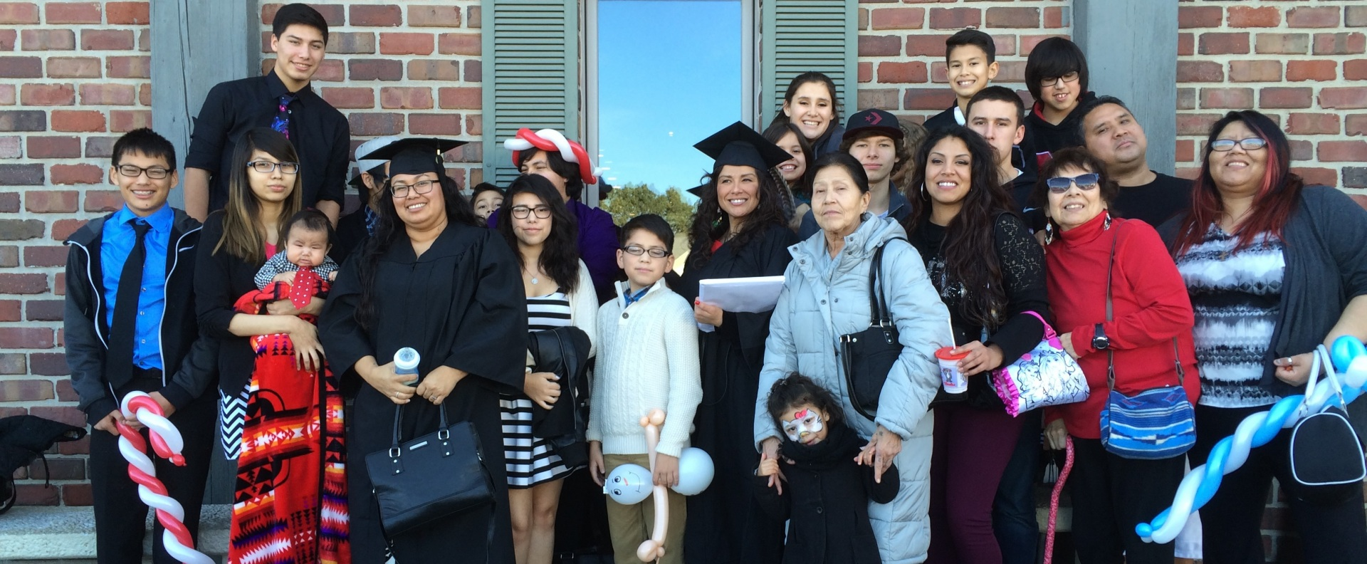 Two gradates in a cap and gown pose for a photograph with their families.