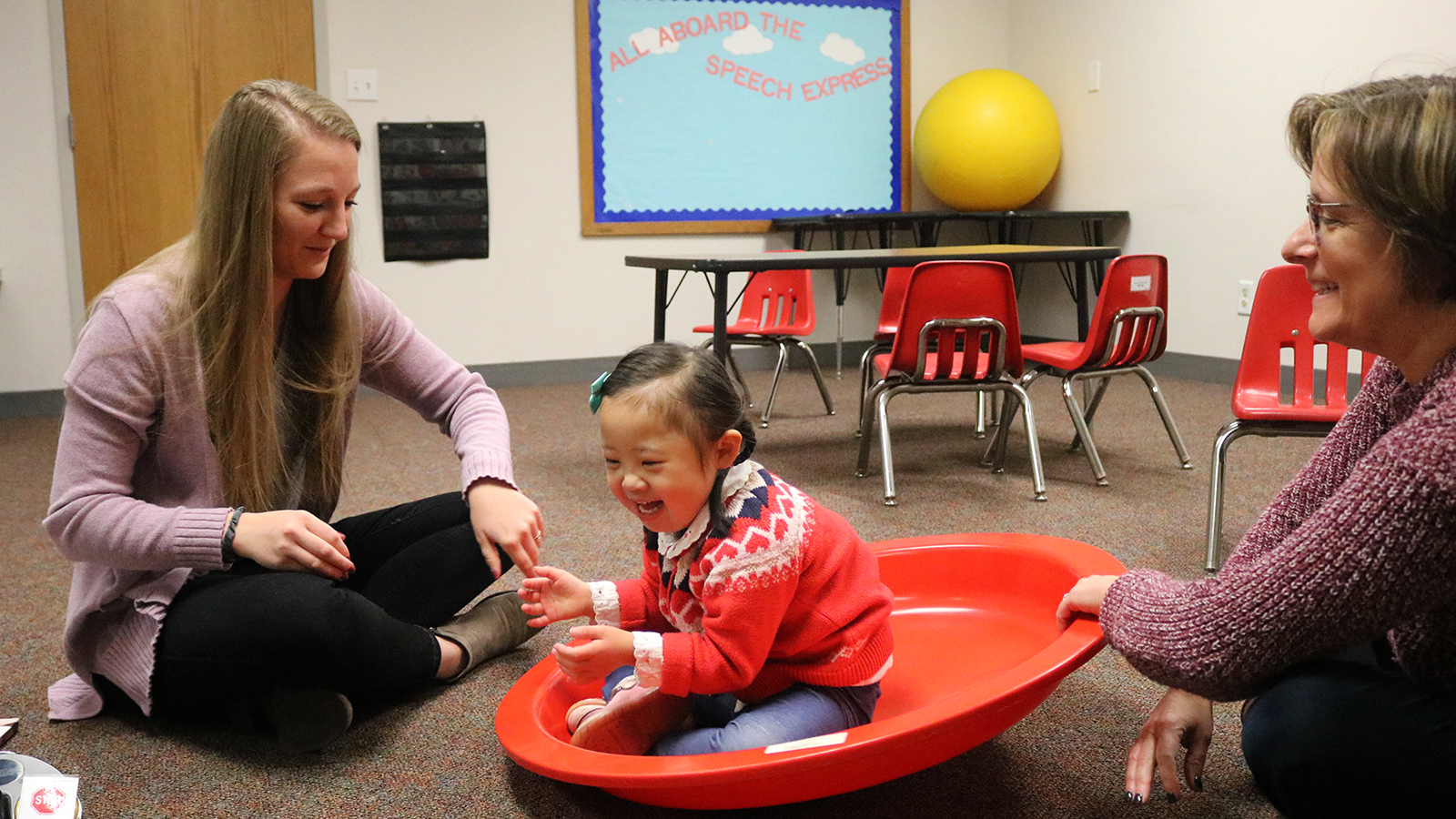 A Husker graduate clinician and her supervisor, Beth Dinneen, share in activities with a young girl with down syndrome during a speech therapy session at the Barkley Speech Language and Hearing Clinic.