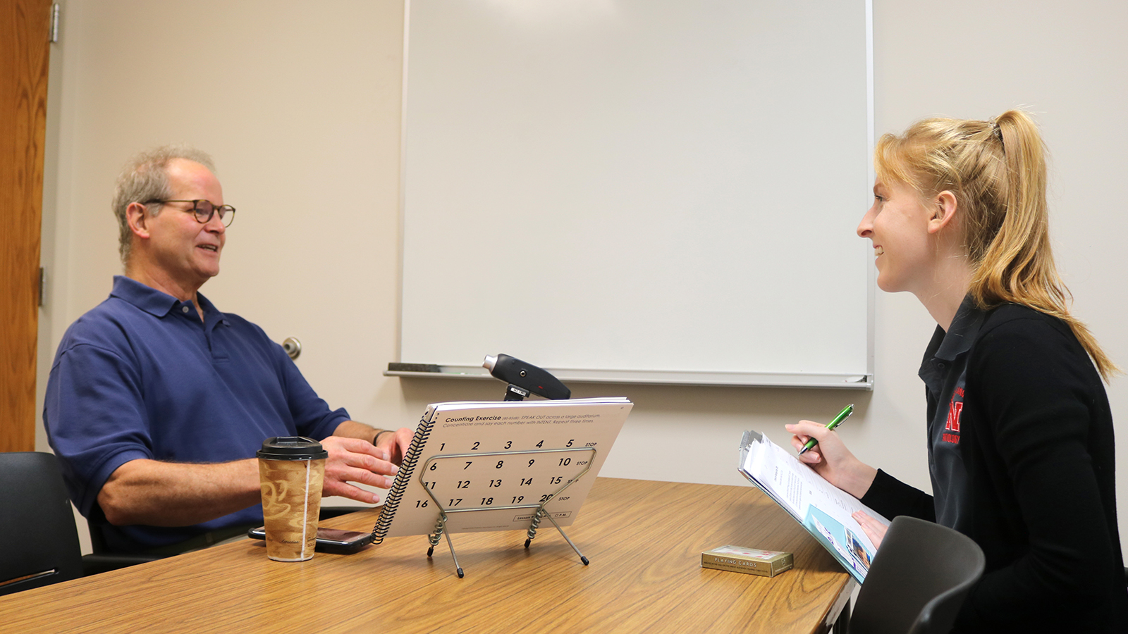 A Husker graduate clinician provides SPEAK OUT!® therapy to a gentleman with Parkinson's.