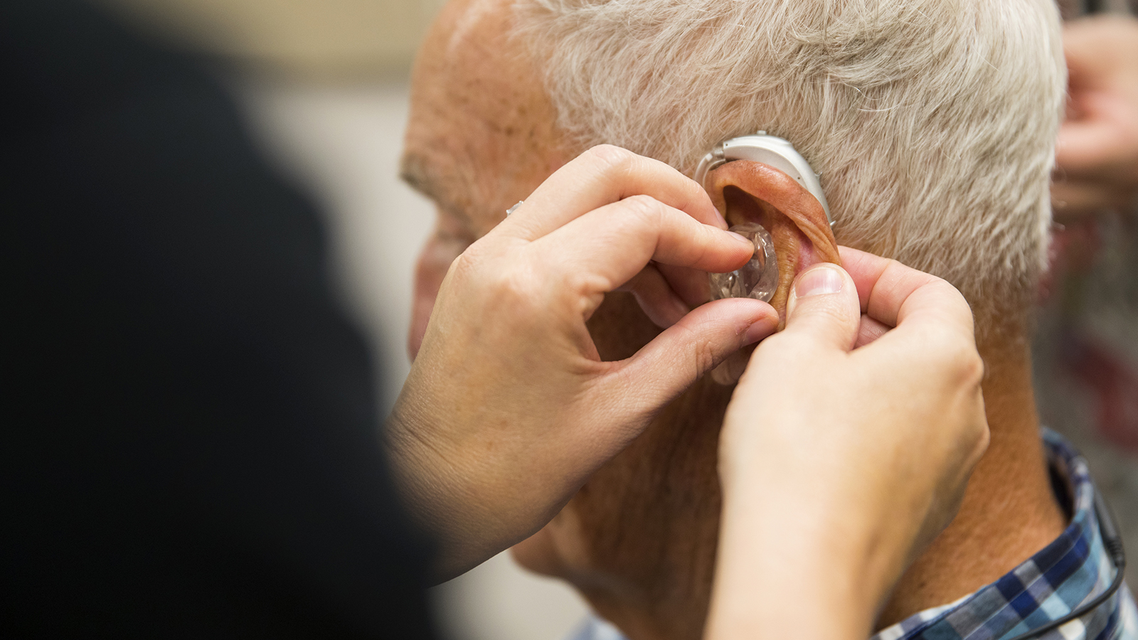 A gentleman is fitted with a hearing aid at the Barkley Speech Language and Hearing Clinic.