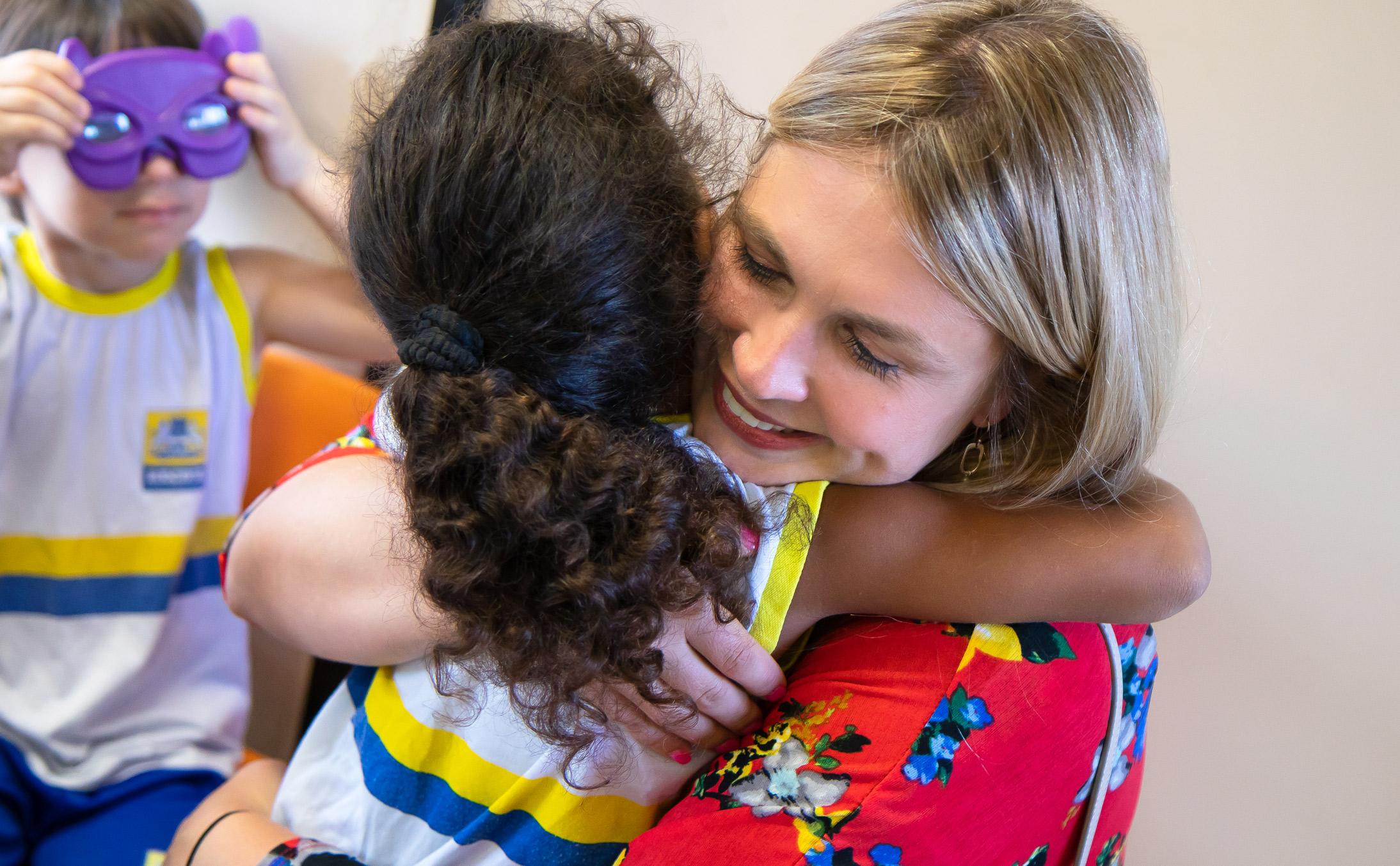 A female adult hugs a child at a nursery school in Brazil.