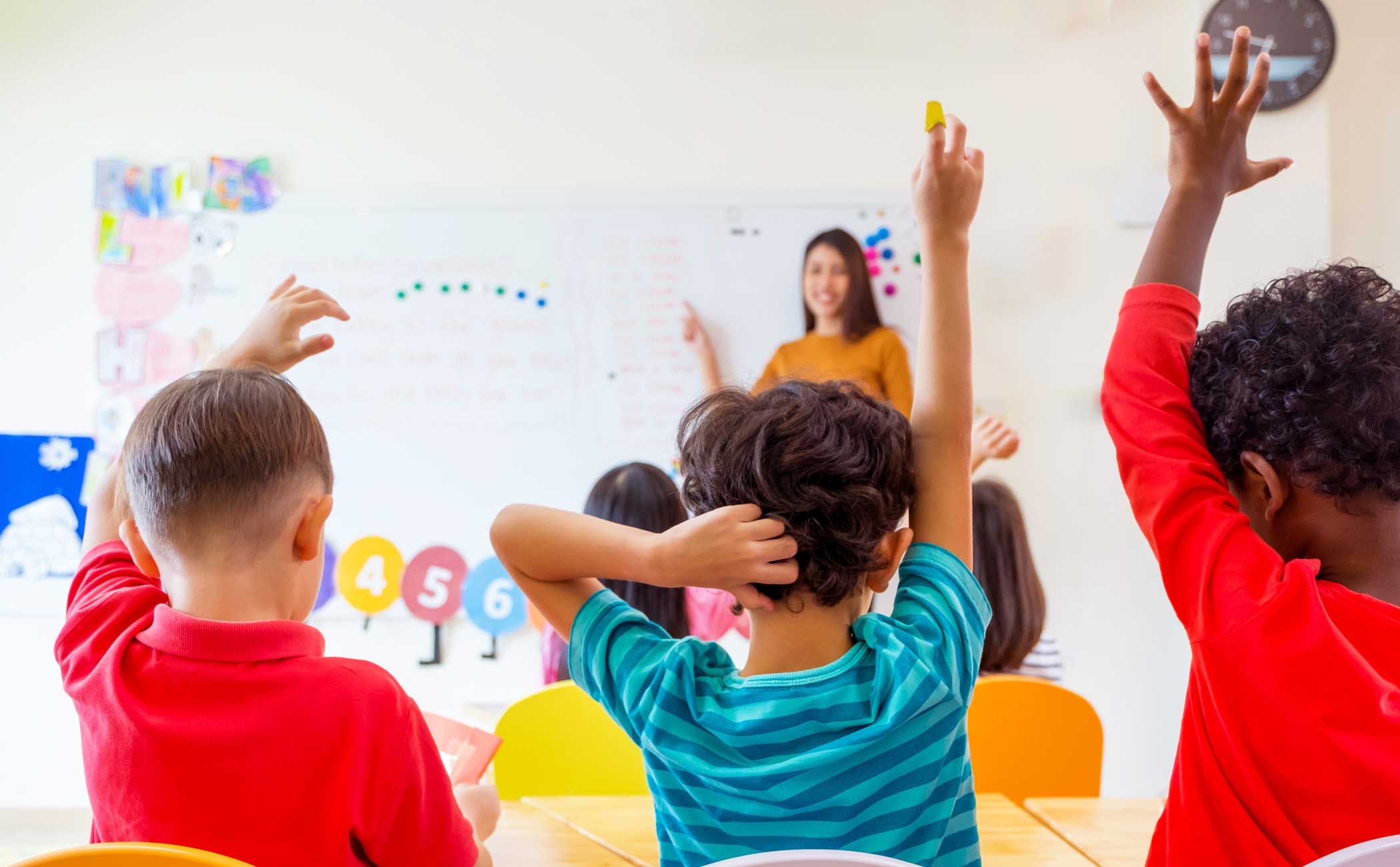 Students in a classroom raising their hands.
