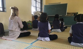 Anubhuti students help teach Jessica Fetrow proper yoga and meditation poses