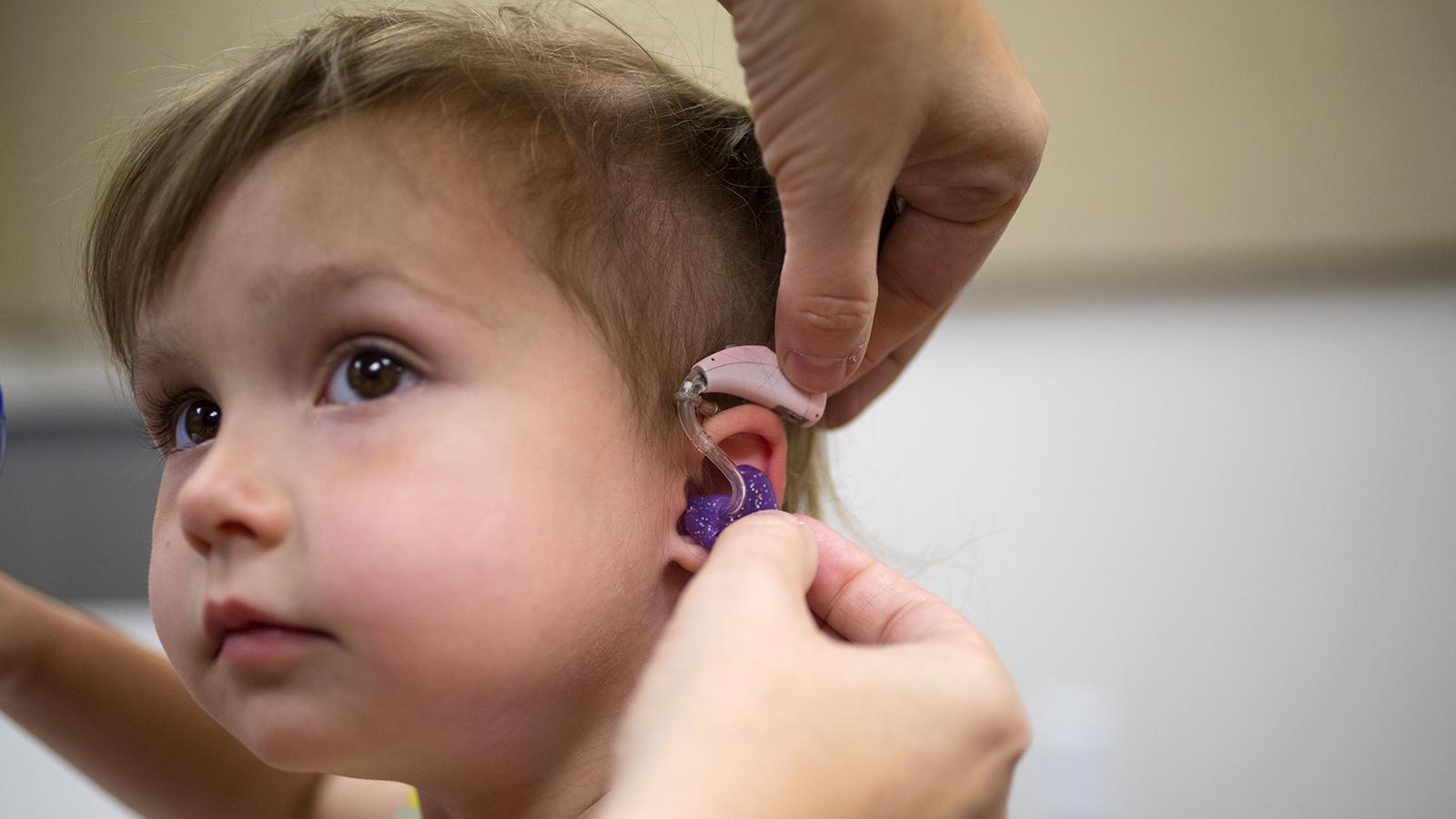 A young girl receives a hearing aid through HearU Nebraska.