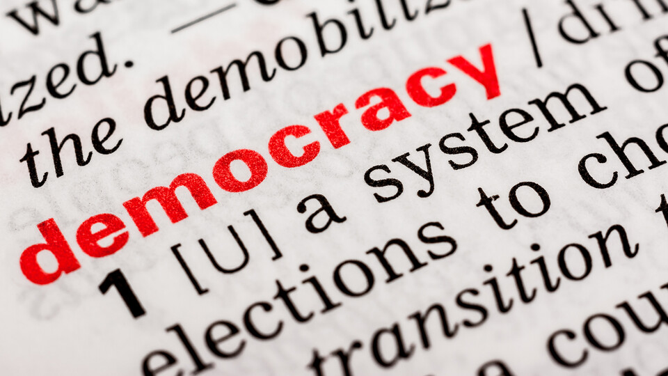 """Words on a page, possibly a dictionary, with the word """"democracy"""" in bold red type."""