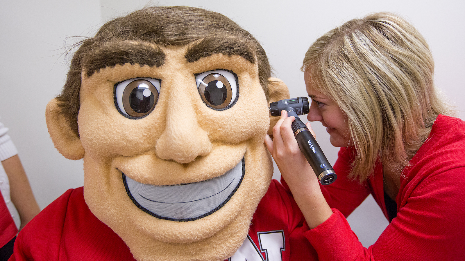Photo of Herbie Husker getting his hearing checked by an audiology student