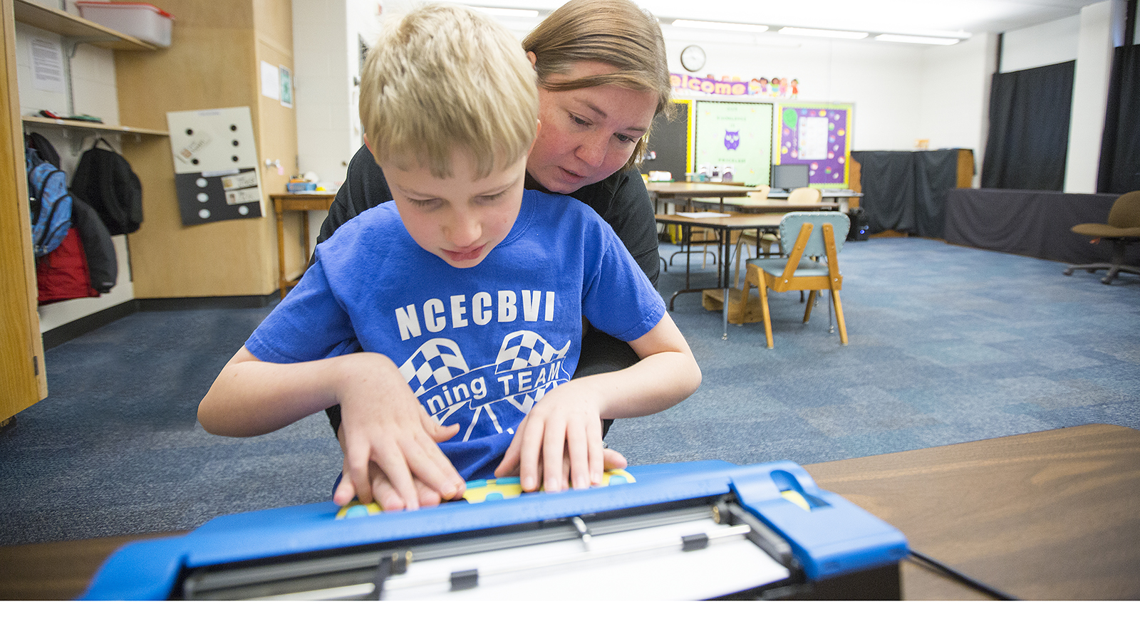 Photo of UNL student teaching a boy to use a Braille Writer typewriter