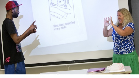 Photo of sign language instructor and student signing to one another
