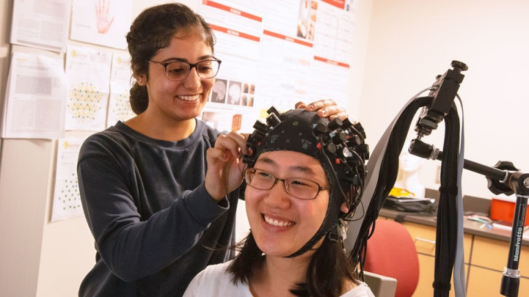 From left, student worker Randa Ismail adjusts a functional near-infrared spectroscopy cap on Grace Oh.
