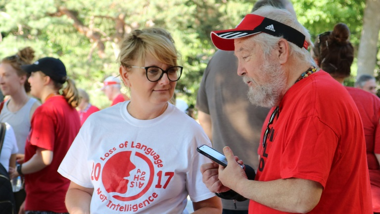 Kristy Weissling speaks with a client from the Barkley Speech Language and Hearing Clinic prior to the start of the 2019 Aphasia Awareness Walk