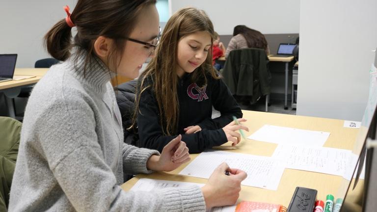 A student at Nebraska tutors a young girl at the Schmoker Reading Center