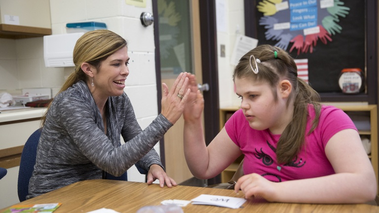 Rachel Zahn (right) gives a high-five to a student at NCECBVI.