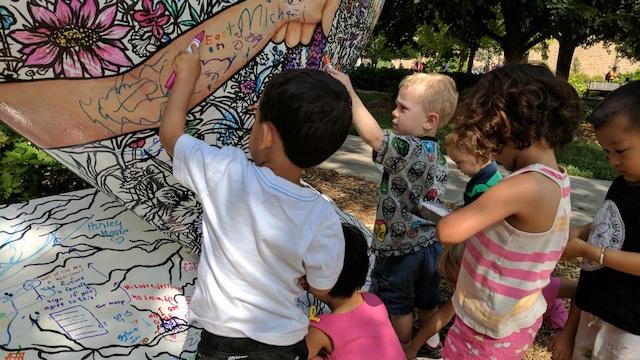Ruth Staples Child Development Lab children color on heart.